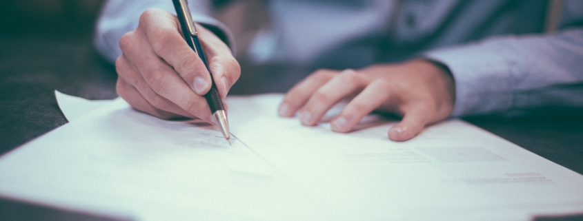 Picture of man writing at a desk
